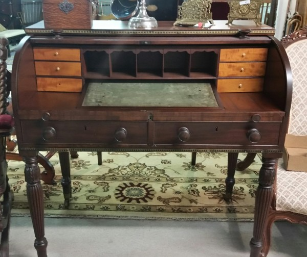 Early 19th Century English Mahogany cylinder roll top desk, with carved & reeded legs, fitted interior, pull our writing surface, and brass inlay.
