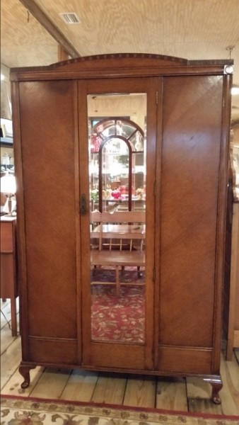 English Antique Oak Armoire with original finish, beveled mirror, and hardware. Beautiful carved crown on top and original makers tag on inside door. The interior has original iron hooks. It sits atop a nice base with Queen Anne style legs.