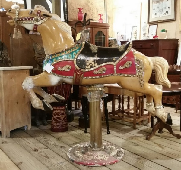 Vintage carousel horse on cast iron Coca-Cola stand.
